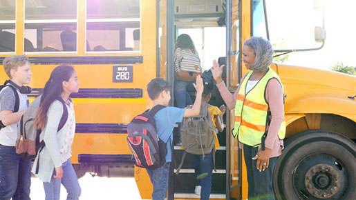 Bus driver greets children boarding bus